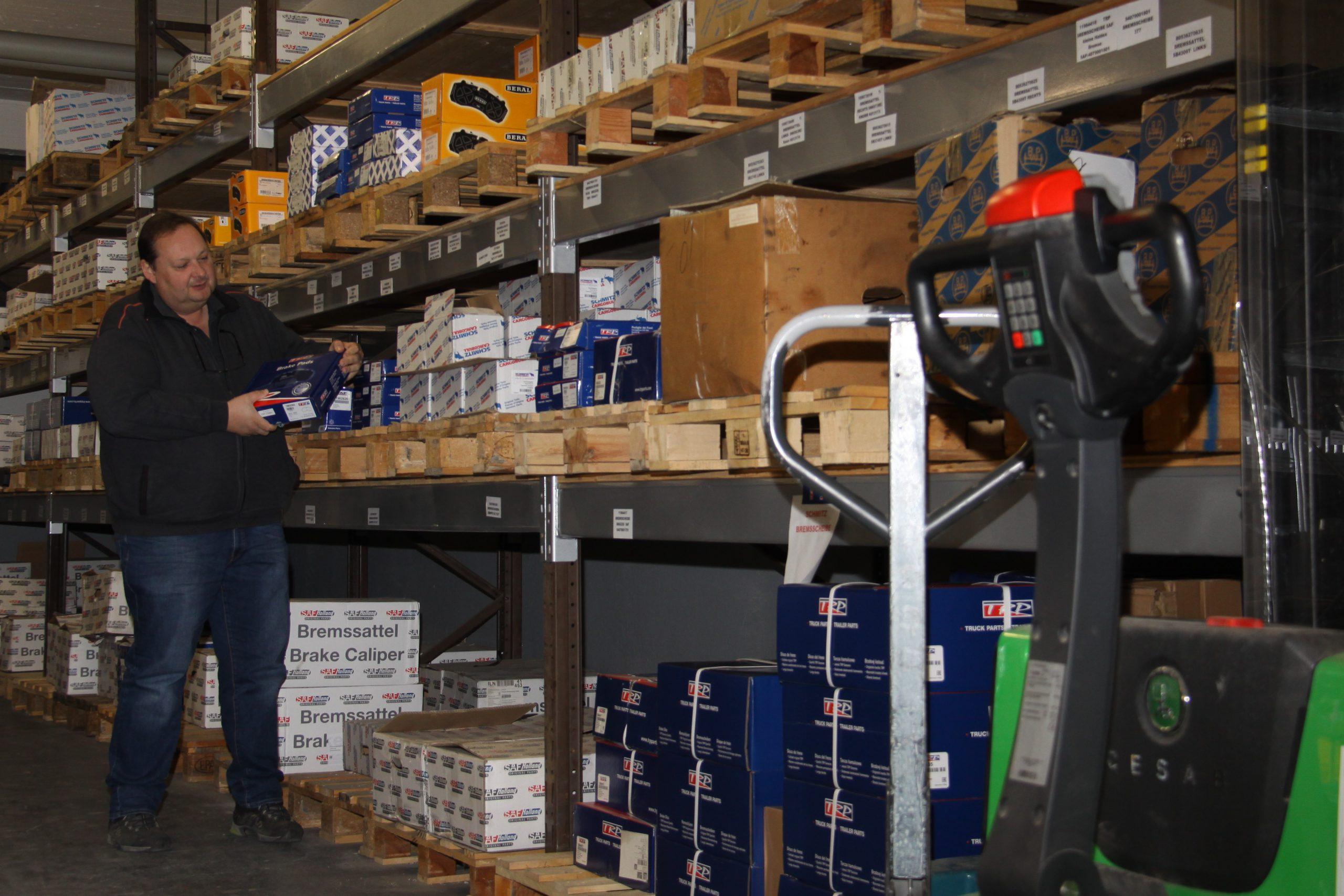 Lagerist vor Regalen mit vielen original Ersatzteilen für DAF LKWs